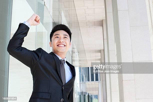 Cheerful businessman punching the air in CBD