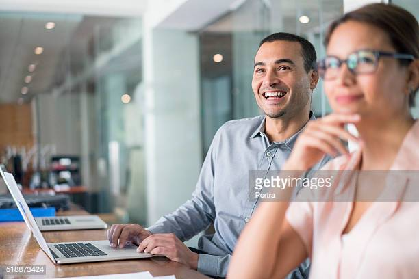 Cheerful businessman using laptop in board room