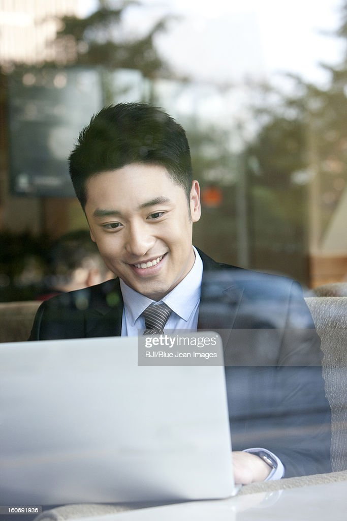 Cheerful businessman using laptop in cafe : Stock Photo
