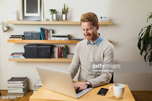 Cheerful businessman using laptop while working from home office