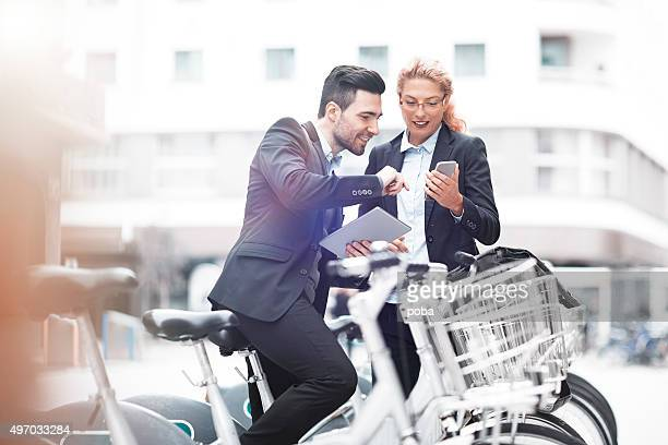 cheerful businessman with bicycle and his colleague overviewing  mobile masages