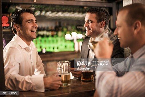 Cheerful businessmen talking in a bar.