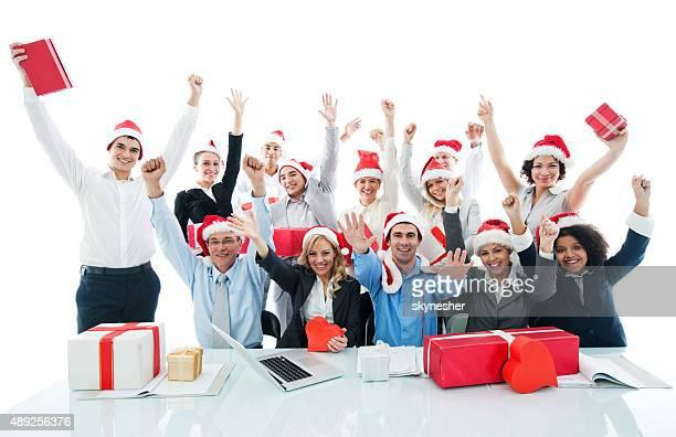 Alegre empresários usando o Pai Natal chapéus e olhando para a câmara.