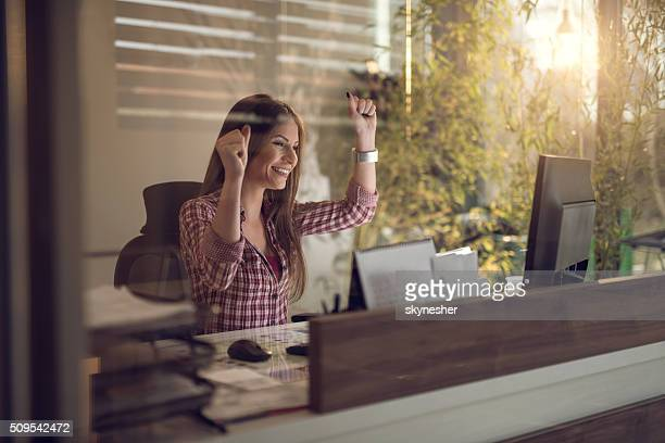 Cheerful businesswoman celebrating success in the office.