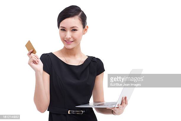 Cheerful businesswoman doing online shopping with laptop and bank card