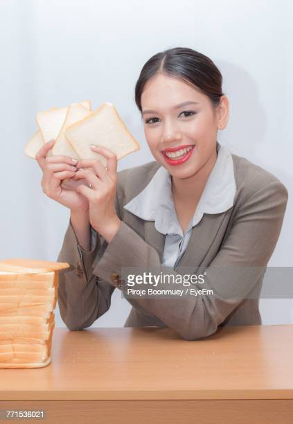 Cheerful Businesswoman Holding Bread Against White Background