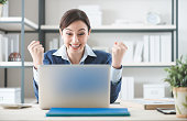 Cheerful businesswoman with raised fists, sitting at office desk and using a laptop, satisfaction and winning concept
