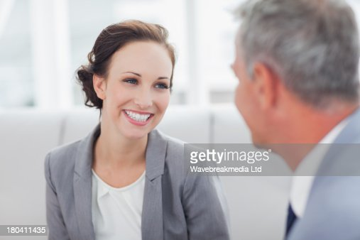 Cheerful businesswoman listening to her workmate talking : Stock-Foto