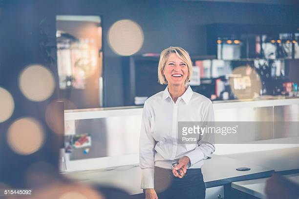 Cheerful businesswoman standing in office
