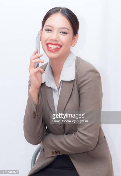 Cheerful Businesswoman Talking On Smart Phone Against White Background