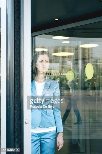 Cheerful Businesswoman Walking Through Revolving Doors