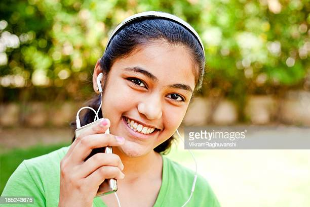 Cheerful Casual Indian Teenage Girl Listening Music on MP3 Player
