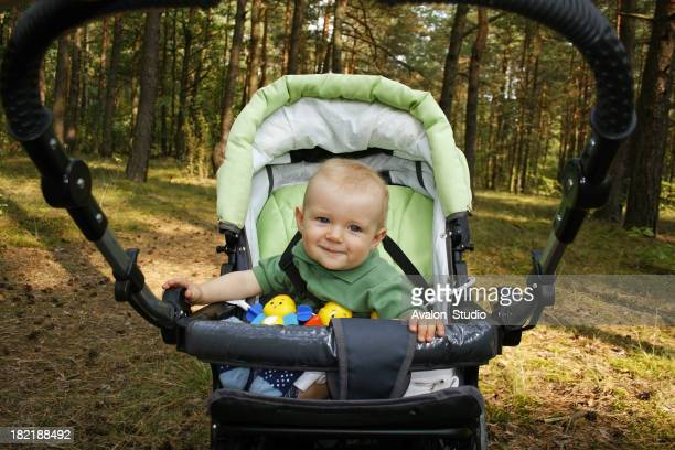 Cheerful child in a stroller on a trip in the forest.