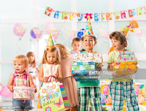 Cheerful children holding birthday presents.