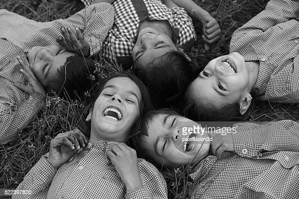 cheerful children lying dawn on grass