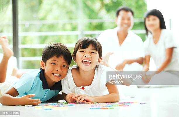 Cheerful children playing with a puzzle at home.