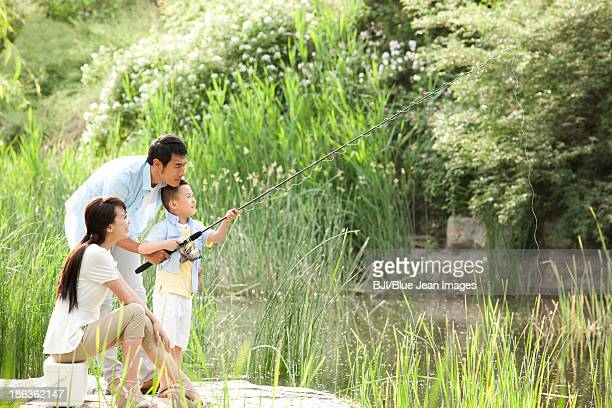 Cheerful Chinese family fishing in a park