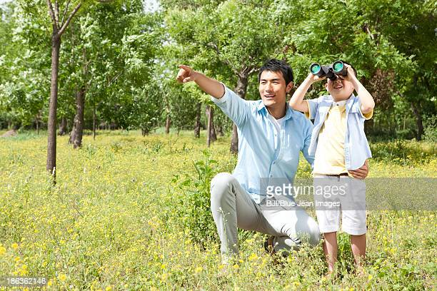 Cheerful Chinese father and son with binoculars in a park