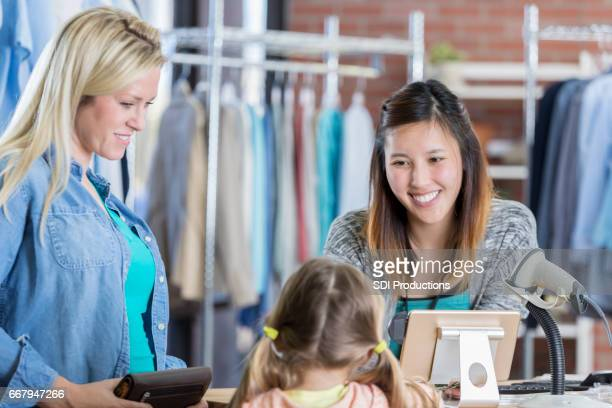 Cheerful clothing store employee talks with young customer