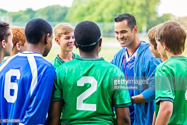 Cheerful coach encourages players before soccer game