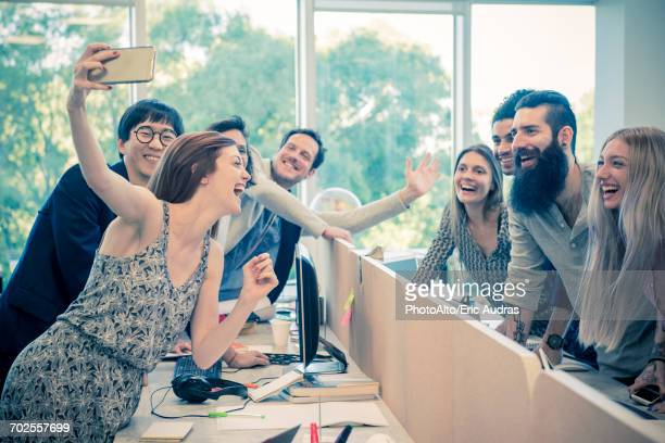Cheerful colleagues posing for a selfie in casual office