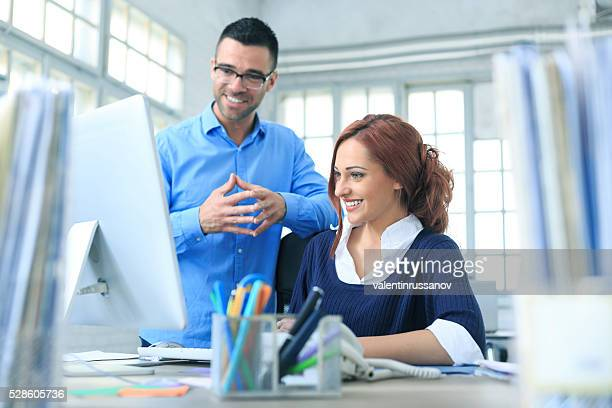Cheerful colleagues using computer in the office