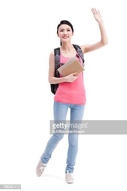 Cheerful college girl waving hand