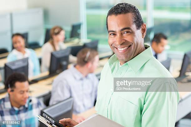 Cheerful continuing education teacher in front of his class