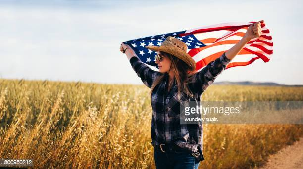 Cheerful country girl waving an American flag in a field