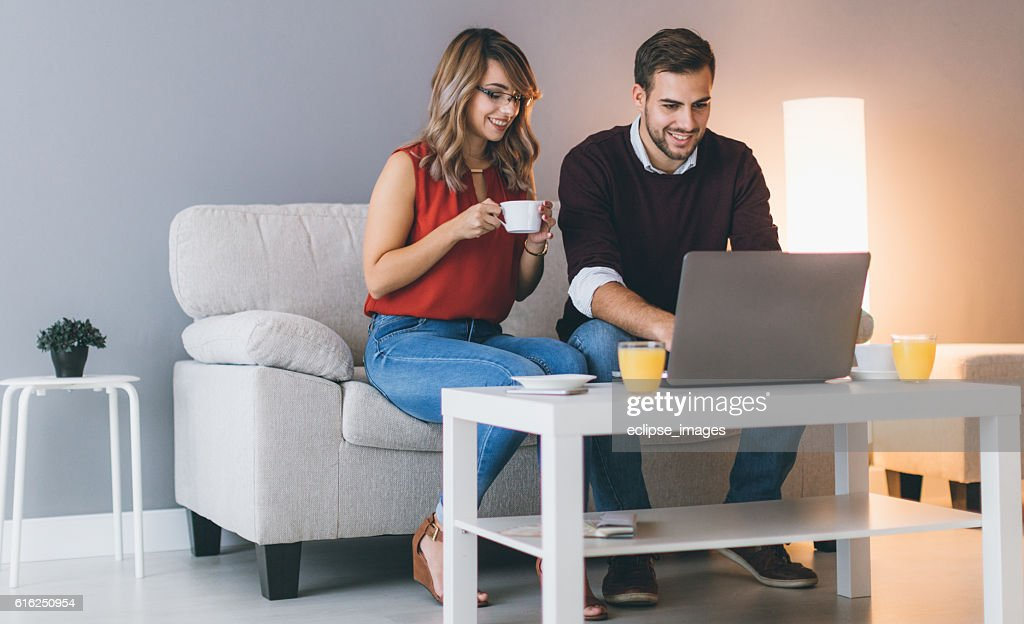 Cheerful couple at home using laptop : Foto de stock