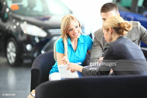 Cheerful couple buying new car.