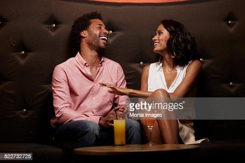 Cheerful couple conversing on sofa at nightclub : Stock Photo