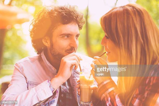 Cheerful Couple Drink One Coffee With Drinking Straw Outdoors.