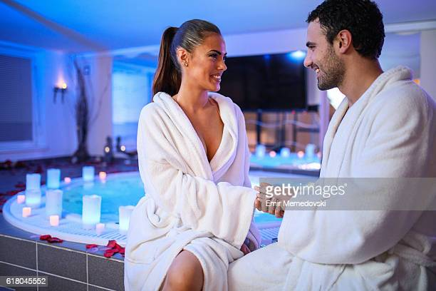 Cheerful couple flirting while sitting outside of hot tub.