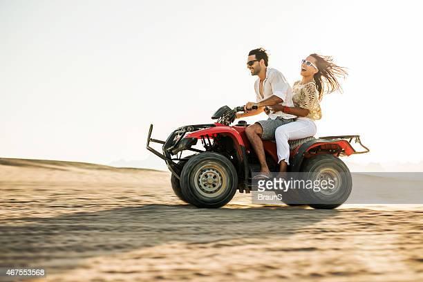 Joyeux couple s'amuser sur un quad.