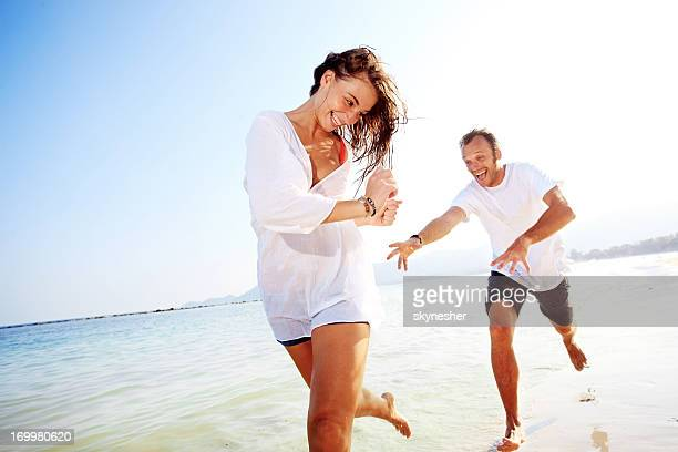 Cheerful couple having fun on the beach.