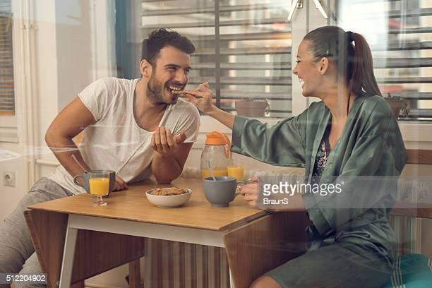 Alegre pareja divirtiéndose juntos durante el desayuno en la cocina.
