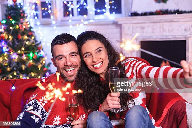 Cheerful couple holding bengal fire and drinking champagne at home