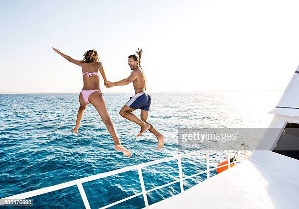 Cheerful couple jumping from boat.