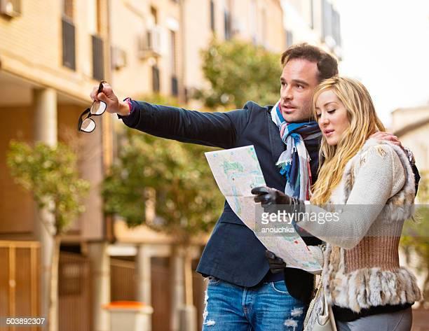Alegre pareja mirando el mapa de la ciudad de Madrid en la calle