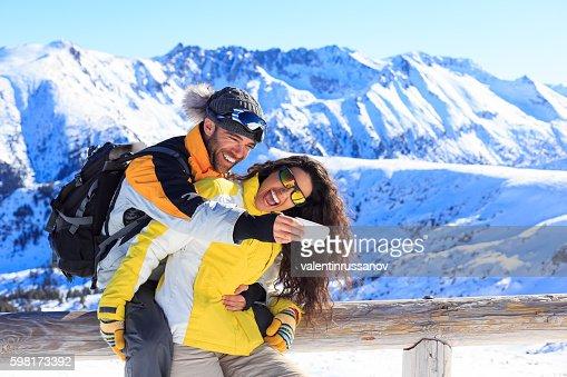 Cheerful couple making selfie in ski resort