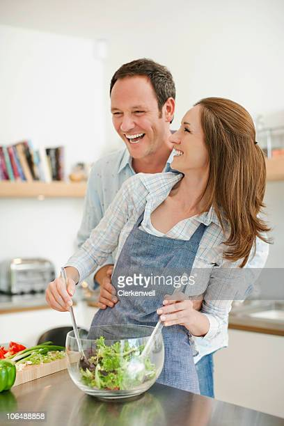 Cheerful couple mixing vegetable salad in kitchen