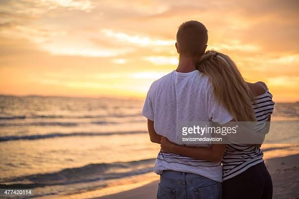 Alegre Pareja en la playa y mirando el atardecer