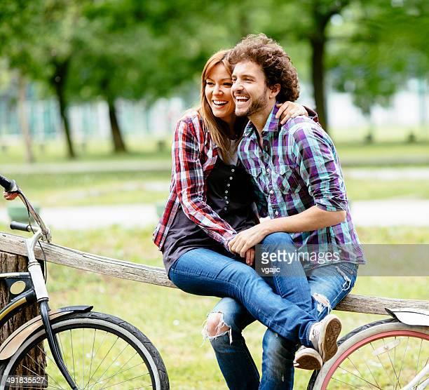 Joyeux couple sur pause après équitation en vélo à l'extérieur.