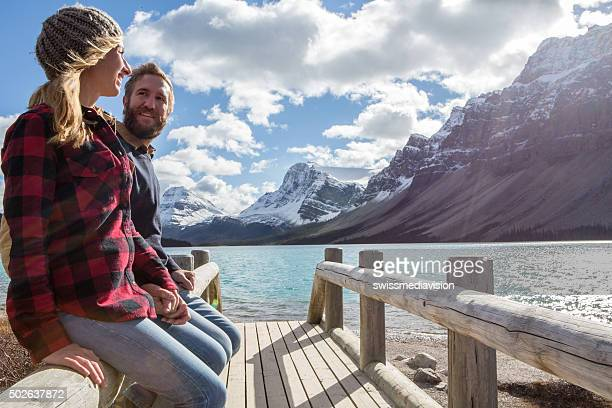 Cheerful couple on log bridge admiring landscape