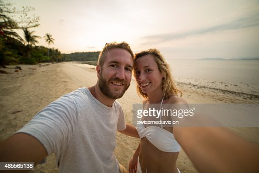 Cheerful couple on tropical beach taking a selfie