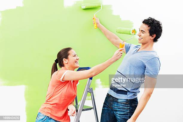 Cheerful couple playing while painting the wall green