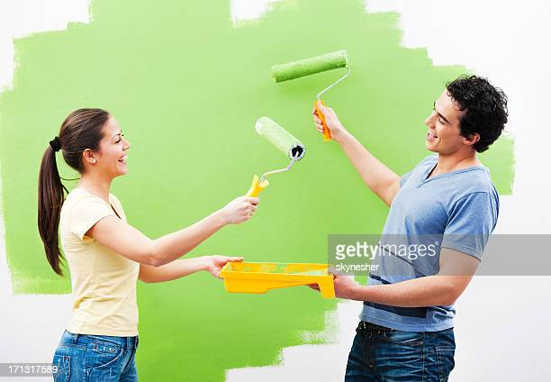 Cheerful couple playing while painting the wall green.