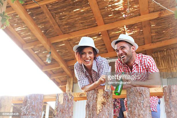 Cheerful couple relaxing and leaning on fence