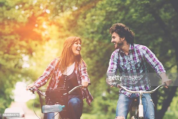 Alegre pareja montando bicicleta juntos.